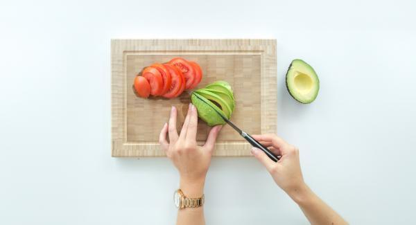 Avocado entsteinen, Fruchtfleisch mit einem Löffel herauslösen und auf den Toasts verteilen.