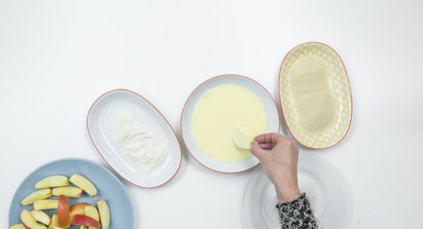 Apfelschnitze nacheinander mit Mehl, Ei-Milch-Mix und Paniermehl panieren.