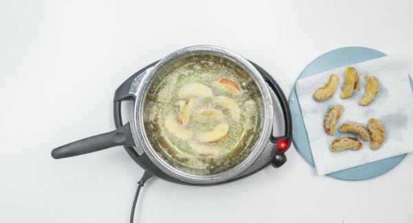 Apfelschnitze wenden und herausnehmen sobald die Schnitze rundherum gold-braun sind. Auf Küchenpapier abtropfen lassen. Mit der zweiten Hälfte der Apfelschnitze wie oben beschrieben verfahren.