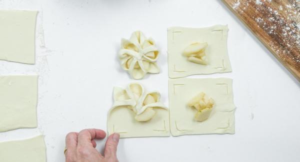 Einige Birnenwürfel in die Mitte geben und die entstandenen Teigränder über den Birnen wie zu einer Blume zusammenfalten und etwas andrücken (siehe Foto).