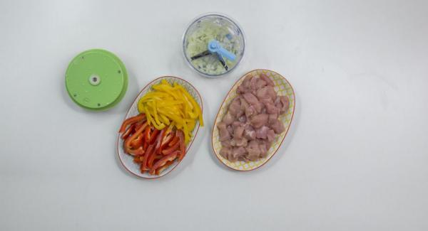 Hähnchen würfeln, Paprika putzen und in Streifen von ca. 3 cm schneiden. Zwiebel schälen und im Quick Cut hacken.
