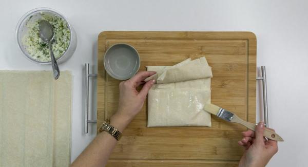 Je 2 Yufka-Teigblätter aufeinander legen und etwas Schafskäsemasse darauf verteilen. Obere und untere Seite mittig einklappen. Rechte Seite überklappen, linke Seite darüber legen und mit etwas Wasser fixieren.