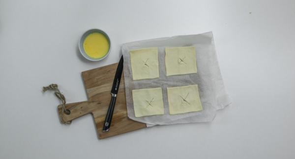 Blätterteig in der Mitte über Kreuz leicht einschneiden oder ein kleines Motiv (z.B. Herz oder Stern) ausstechen. Eigelb und Milch verrühren.