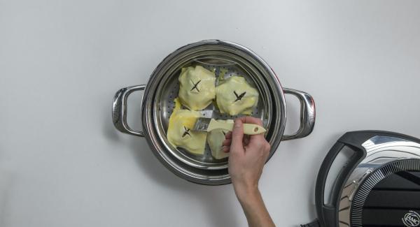 Apfelhälften mit Pekannüssen und Cranberries füllen. Je ein Blätterteig-Quadrat auflegen und mit verquirltem Ei bestreichen.