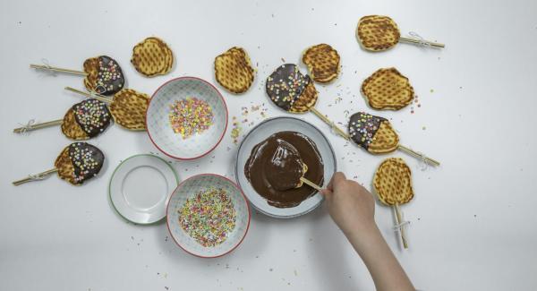 Die Waffeln auf Spiesse stecken, in flüssige Schokolade tauchen und dann mit bunten Streusseln verzieren.