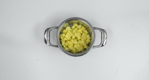 Kartoffelwürfel tropfnass in einen Topf geben und Möhren im Siebgareinsatz darüber setzen.