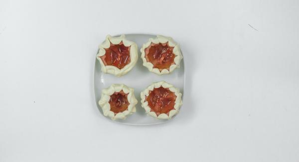 Pizzateig dünn ausrollen und Kreise etwas grösser als die Tomate ausstechen. Z.B. mit einem Glas. Teigkreise bis zur Schnittkante fest um die Tomate wickeln.