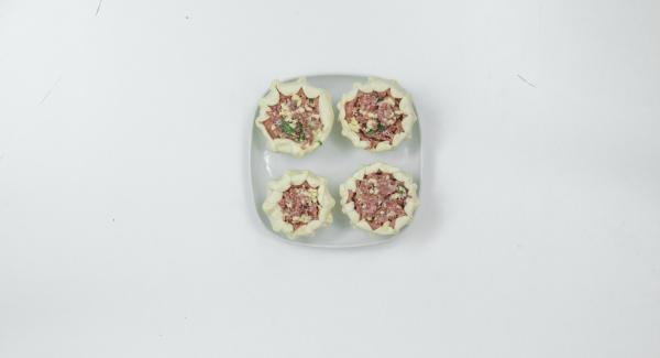 Für die Füllung Salami mit Petersilie im Quick Cut zerkleinern. Hälfte des Käses untermischen und in Tomaten verteilen. Mit restlichem Käse bestreuen.