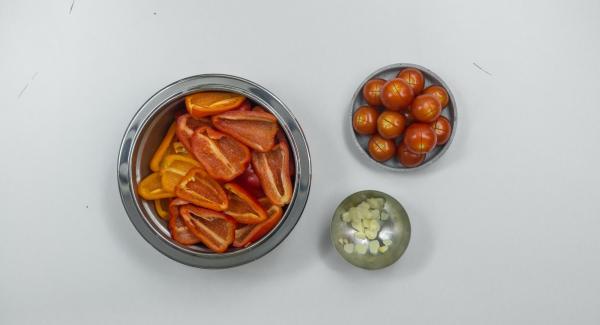 Paprikaschoten putzen, entkernen, gut trocken tupfen und falls nötig klein schneiden. Tomatenhaut an der Oberseite kreuzweise leicht einritzen. Knoblauch schälen und in Scheiben schneiden.