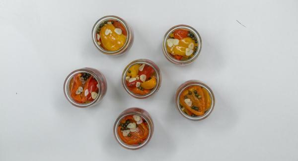 Cocktailtomaten in Weckgläser geben, Paprikastücke einfüllen, je einen halben Teelöffel grünen Pfeffer zufügen und Sud darüber verteilen. Gläser dabei nur zu einem Drittel mit Sud füllen.
