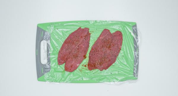 Schnitzel zwischen Frischhaltefolie legen und flach klopfen, dann würzen.