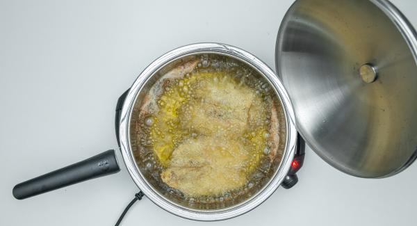 Mit Hilfe des Audiotherms frittieren bis der Wendepunkt bei 90° C erreicht ist. Schnitzel wenden, fertig frittieren bis sie gold-braun sind.