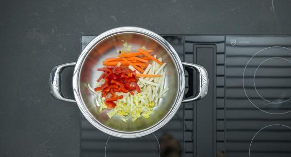 Sobald der Audiotherm beim Erreichen des Brat-Fensters piepst, auf niedrige Stufe schalten und Ingwer-Zwiebelmischung  unter Rühren anbraten, alle Gemüsestreifen nach und nach zugeben und unter Rühren mitbraten.