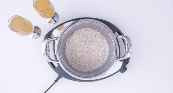 Reis, Meeresfrüchte und Brühe in Topf geben.