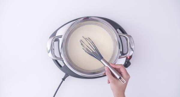 Restliche Zitronenschale zu Ei-Masse geben und unter die heiße Milch rühren.