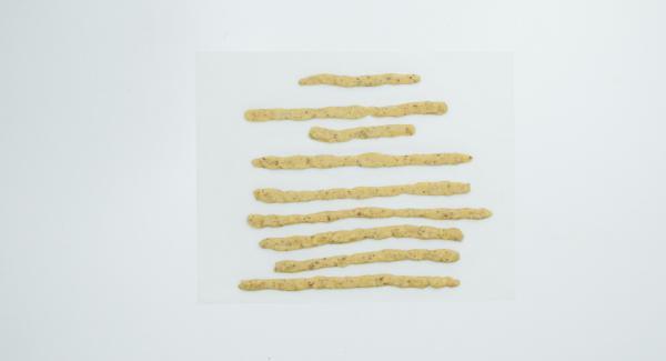 Mit Hilfe des ovalen Deckels einen ovalen Kreis aus Backpapier zuschneiden der 2 cm breiter ist als die Bodenfläche. 3/4 des Teiges auf Backpapier verteilen (am besten mit den Händen). Den restlichen Teig in 8 Stücke teilen und zu Streifen formen für die Dekoration.