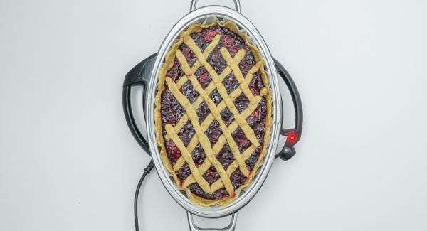 Sobald der Audiotherm beim Erreichen des Brat-Fensters piepst, auf Stufe 1 schalten, Backpapier mit Teig einlegen, mit Konfitüre bestreichen, die Teigstreifen in Form eines Rautenmuster darauf legen und Deckel auflegen.