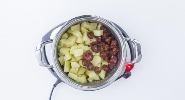Chorizo und Kartoffeln hinzufügen, umrühren und Fleischbrühe zugeben. Deckel aufsetzen.