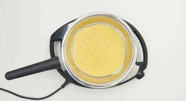Sobald der Audiotherm beim Erreichen des Brat-Fensters piepst, Navigenio ausschalten. Hälfte der Eimischung in die HotPan giessen, die Hälfte der anderen Zutaten darüberverteilen und einen Esslöffel Käse darüberstreuen.