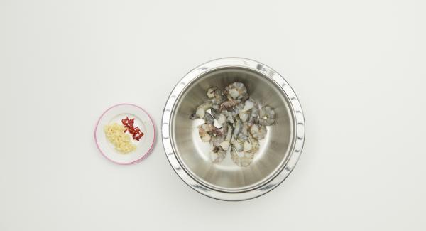 Garnelen vorbereiten, falls nötig am Rücken einschneiden und schwarzen Darmfaden entfernen. Knoblauch schälen, Chili putzen, beides fein hacken und mit Garnelen und 2 Esslöffeln Olivenöl mischen.