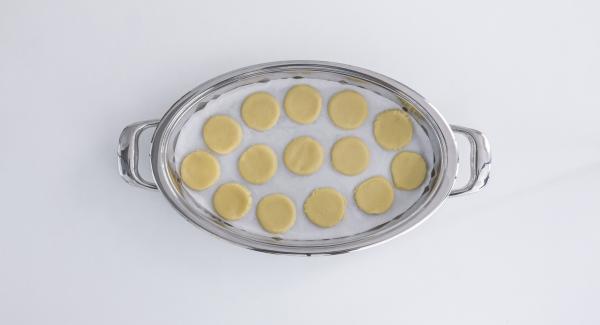 Ein oval zugeschnittenes Backpapier in den kalten Ovalen Griddle legen und Kekse darauf legen.
