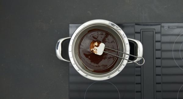 Schokolade in Stücke brechen, zusammen mit Butter in eine Kombischüssel geben und auf mittlerer Stufe im Wasserbad schmelzen. Schokoladenmischung dann lauwarm abkühlen lassen.