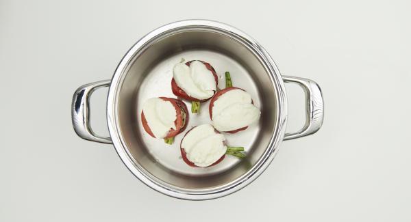 Gemüse- und Mozzarellascheiben sowie Zwiebelstücke direkt im Topf abwechselnd zu vier kleinen Türmen zusammensetzen, dabei zwischen den Lagen mit etwas Parmesan bestreuen. Zum Schluss eine Scheibe Mozzarella auf das Türmchen legen.