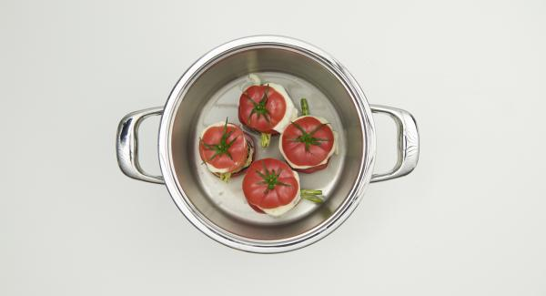 Zum Servieren einen Spiegel aus Pesto auf den Teller geben und ein Gemüse-Türmchen darauf setzen. Zum Schluss die Deckel der Tomaten aufsetzen und warm servieren.