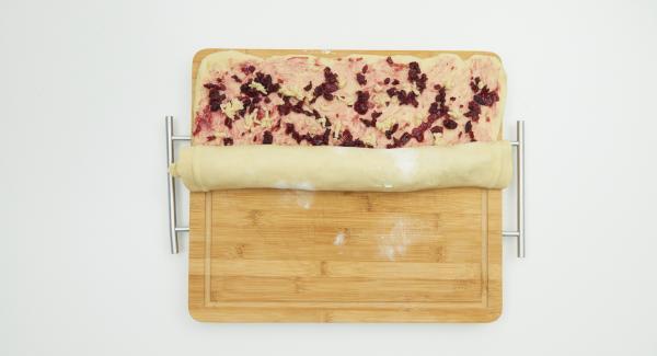Alles von der Längsseite her aufrollen, zu einem Kranz formen und mit dem Backpapier in den Topf legen. Kranz mit einer Schere an der Oberfläche einschneiden, mit Milch einpinseln und mit Hagelzucker und Mandelblättchen bestreuen.