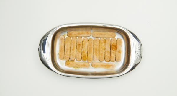 Eine Lage Löffelbiskuits in die mittlere Lasagnera geben, die Hälfte der Orangensauce darübergeben und die Löffelbiskuits einweichen lassen.