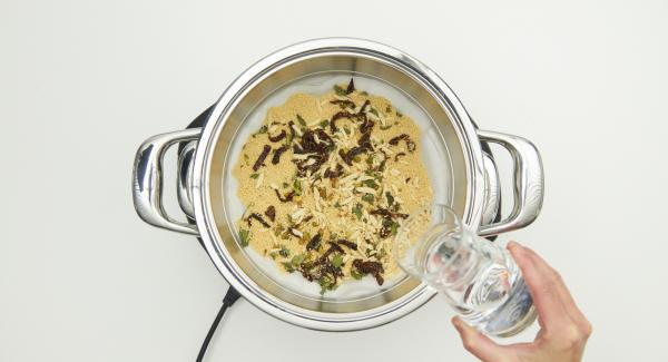 Kombisieb-Einsatz auf den Topf setzen und ca. 100 ml Wasser über dem Couscous verteilen.