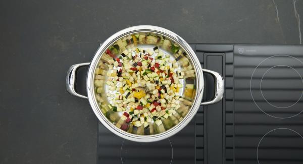 Sobald der Audiotherm beim Erreichen des Brat-Fensters piepst, auf niedrige Stufe schalten, Zwiebelmischung anbraten. Tintenfischwürfel zufügen, kurz mit anbraten, dann aus der HotPan nehmen. Gemüsewürfel ebenfalls anbraten, mit Salz und Pfeffer würzen, gehackte Tomaten und Kräuter unterrühren.