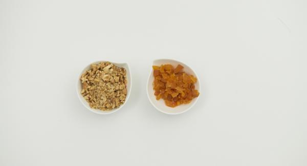 Aprikosen würfeln, Walnüsse grob hacken und beides zusammen mit Cranberries über das Obst geben. Nach Belieben mit Zucker und Zimt bestreuen.
