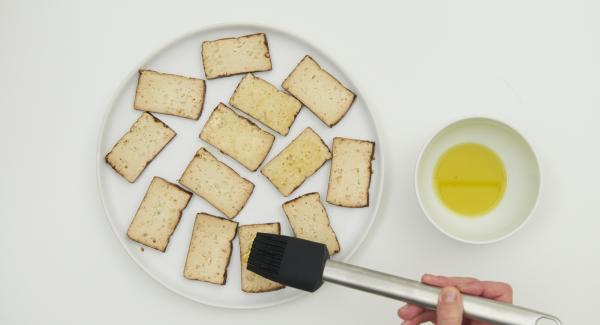Tofu in vier große oder mehrere kleine Scheiben schneiden und mit dem restlichen Öl einpinseln.