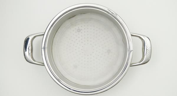 Mit Hilfe des Kombi-Siebeinsatz oder eines Deckels 24 cm einen Kreis aus Backpapier ausschneiden und in den Kombi-Siebeinsatz legen.