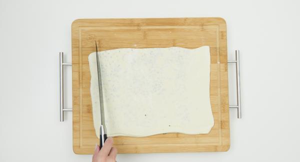 Teigplatte auf einer Hälfte mit Rosmarin, Parmesan und Salz bestreuen. Andere Hälfte darüberklappen, mit einem Nudelholz etwas mehr ausrollen. Teigplatte nochmals zusammenklappen und ausrollen. Teigplatte in ca. 2 cm breite Streifen schneiden.
