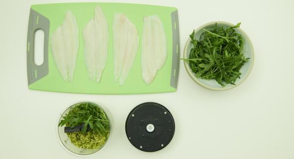 Fischfilets auf einem Brett bereit legen. Parmesan und Pistazien in den Quick Cut geben und fein hacken. Rucola dazugeben und klein hacken. Olivenöl zugeben, mit Salz und Pfeffer würzen und mischen.