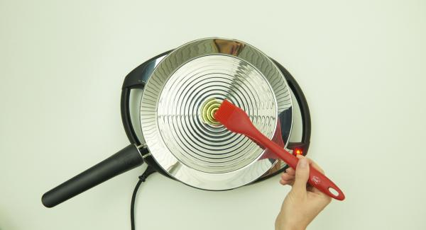 Auf mittlere Stufe/Flamme schalten und Fett hineingeben. Gleichmäßig in der oPan large verteilen.