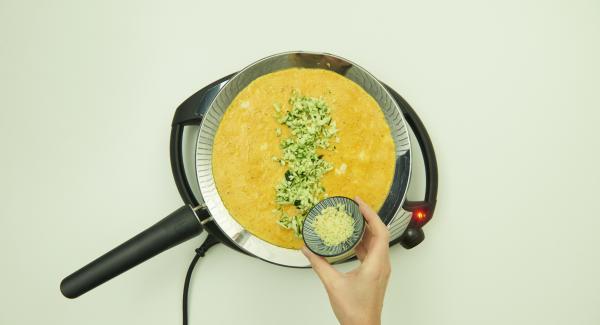 Noch bevor die Masse in der oPan large komplett gestockt ist, Zucchini und Käse in der Mitte des Omeletts verteilen.