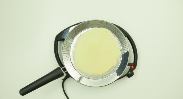 Auf mittlere Stufe/Flamme schalten, Menge für einen Pfannkuchen in die oPan large geben und gleichmässig durch Wenden der Pfanne verteilen.