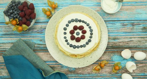 Bestreichen Sie jeden Pfannkuchen mit der Masse und legen Sie diese aufeinander. Servieren Sie die Pfannkuchentorte garniert mit der restlichen Masse und frischen Früchten.