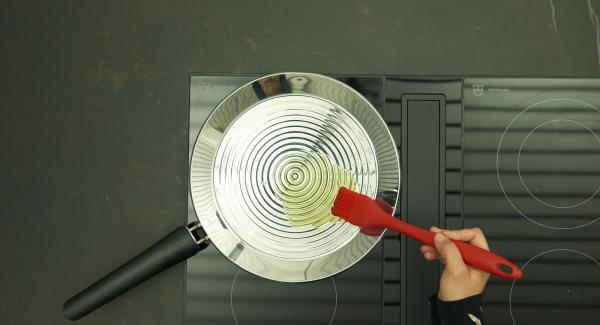Auf mittlere Stufe/Flamme schalten und Fett hineingeben. Gleichmässig in der oPan large verteilen.