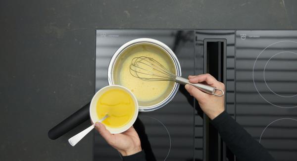 Für die Sauce Eigelbe mit einem Schneebesen unter den Weinsud schlagen. Herd auf niedrige Stufe schalten, langsam nach und nach lauwarme Butter zugeben.