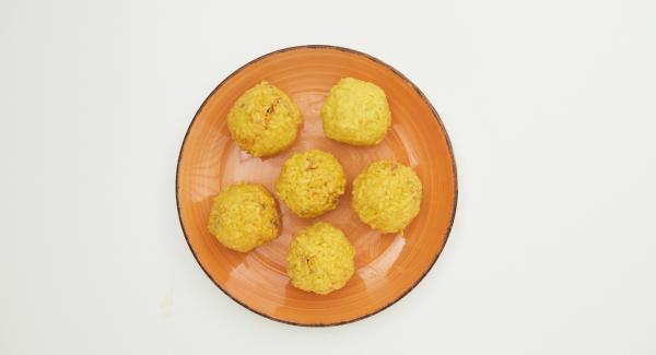 Ein Sechstel vom Risotto auf die Handfläche geben, flach drücken und ein Sechstel der Füllung darauf geben, sorgfältig mit dem Reis einhüllen und zu einer Kugel rollen.