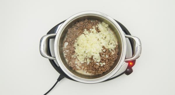 Sobald der Audiotherm beim Erreichen des Brat-Fensters piepst, auf Stufe 3 schalten und das Hackfleisch portionsweise krümelig anbraten. Zwiebel und Knoblauch zugeben und mit anbraten. Zucchini zugeben und ca. 2 Minuten mitbraten.