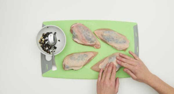 Bei den Hähnchenbrüsten vorsichtig mit den Fingern über eine Öffnung die Haut vom Fleisch lösen und Knoblauch-Olivenmischung einfüllen, fest andrücken.