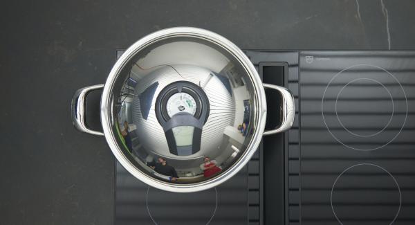 Sobald der Audiotherm beim Erreichen des Brat-Fensters piepst, auf niedrige Stufe schalten und Hähnchenbrüste mit Hautseite nach unten einlegen. Deckel auflegen und braten bis der Wendepunkt bei 90 °C erreicht ist. Restlichen Knoblauch mit Messerrücken andrücken.