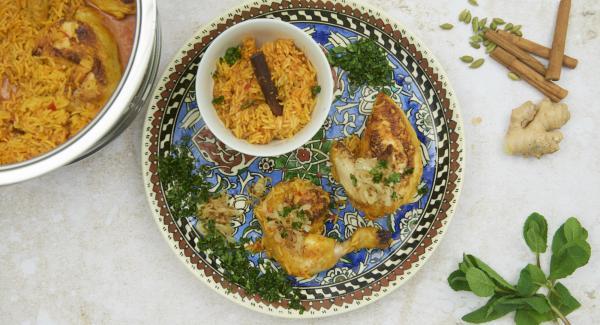 Koriander- und Pfefferminzblätter abzupfen und fein hacken. Hähnchen-Pilaw abschmecken und mit Kräutern und Zwiebeln servieren.