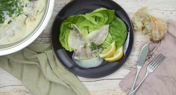 Fisch in die heisse Sauce geben, auf niedrige Stufe schalten und mit aufgelegtem Deckel je nach Grösse der Filets ca. 5 Minuten ziehen lassen. Kräuterblättchen fein hacken, zugeben, abschmecken und servieren.