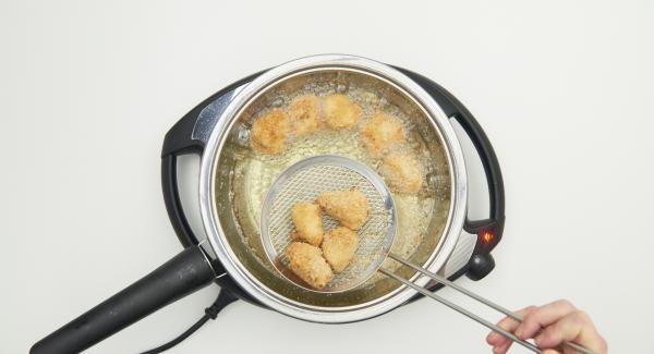 Nuggets kurz wenden, herausnehmen sobald sie gold-braun sind und auf Küchenpapier abtropfen lassen. Mit der zweiten Portion ebenso verfahren.